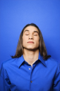 Royalty Free Photo of a Teen Boy Standing Against a Blue Background With His Eyes Closed