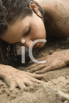 Royalty Free Photo of a Woman Lying in Sand