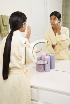 Royalty Free Photo of a Young Woman Looking in the Mirror Applying a Facial Scrub