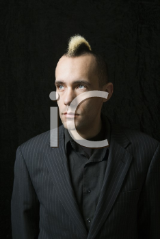 Royalty Free Photo of a Man in a Suit With Mohawk Against a Black Background