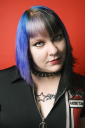 Royalty Free Photo of a Woman With Blue Hair, Tattoos, and a Spike Collar Against an Orange Background