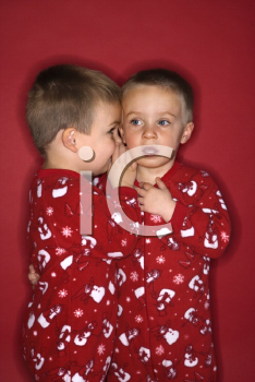 Royalty Free Photo of a Twin Whispering to His Twin