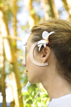 Royalty Free Photo of a Woman Wearing a Plumeria Flower Behind Her Ear