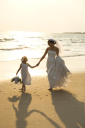 Royalty Free Photo of a Bride and Flower Girl Holding Hands Walking Barefoot on a Beach