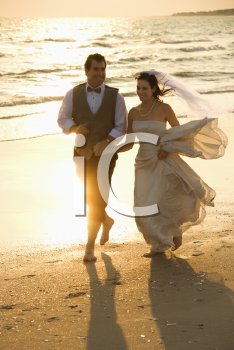 Royalty Free Photo of a bride and mid-adult groom holding hands running barefoot on beach.