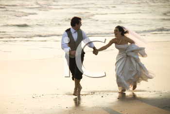 Royalty Free Photo of a Groom and Bride Running Barefoot on a Beach