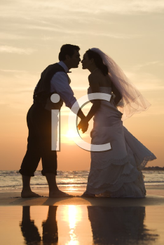 Royalty Free Photo of a Bride and Groom Holding Hands and Kissing Barefoot on a Beach at Sunset