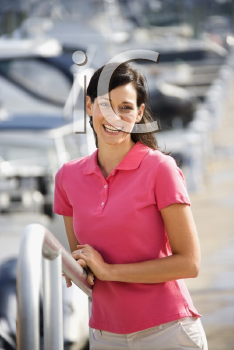 Royalty Free Photo of Female Smiling at a Camera and Holding a Railing at a Harbor