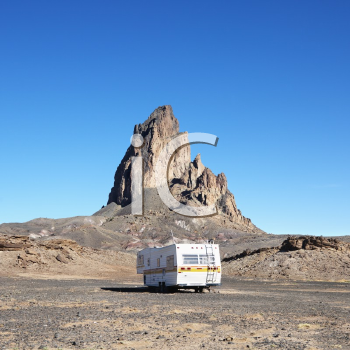 Royalty Free Photo of an RV Traveling Toward a Rock Formation in the Desert of Monument Valley, Utah