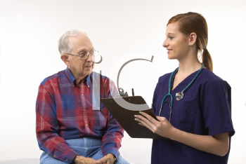 Royalty Free Photo of a Woman in Scrubs Taking Notes From an Elderly Man