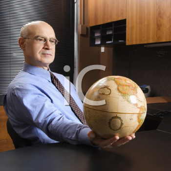 Royalty Free Photo of a Middle-aged Businessman Sitting at a Desk in an Office Holding a Globe