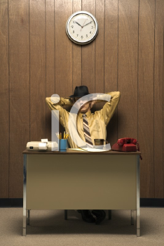 Royalty Free Photo of a Retro Businessman Sitting at a Desk Wearing a Fedora