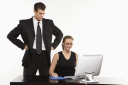 Royalty Free Photo of a Man With Hands on Hips Looking Over Shoulder of a Woman Sitting at Computer