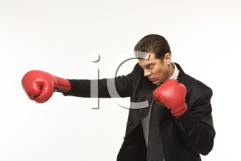 Royalty Free Photo of a Man Wearing a Suit and Punching with Boxing Gloves