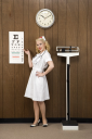 Royalty Free Photo of a Female Nurse Pointing to an Eye Chart