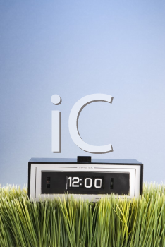 Royalty Free Photo of a Studio Shot of a Retro Alarm Clock Placed in the Grass