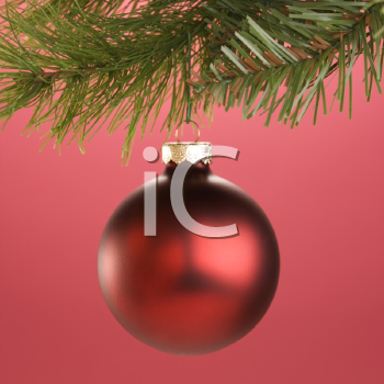 Royalty Free Photo of a Round Red Christmas Ornament Hanging From a Pine Branch