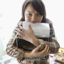 Royalty Free Photo of a Woman Holding a Typewriter and Biting a Page
