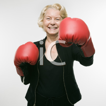 Royalty Free Photo of an Older Woman Wearing Boxing Gloves and Throwing Punches