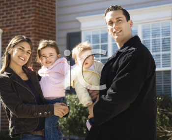 Royalty Free Photo of a Family Standing in Front of a House