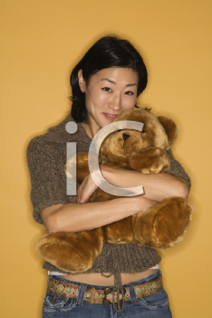 Royalty Free Photo of a Pretty Woman Hugging a Brown Teddy Bear