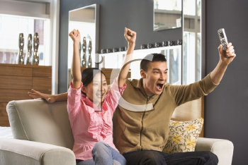 Royalty Free Photo of an Asian Couple Cheering While Watching Television