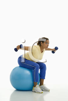 Royalty Free Photo of a Woman Balancing on an Exercise Ball With Outstretched Arms Holding Dumbbells