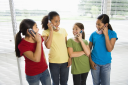 Royalty Free Photo of Preteen Girls Talking on Cellphones