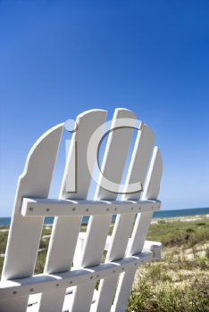 Royalty Free Photo of an Empty White Adirondack Chair Facing the Beach
