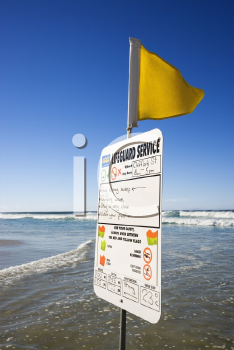 Royalty Free Photo of a Sign and Flag on a Beach in Surfers Paradise, Australia with Lifeguard Schedule