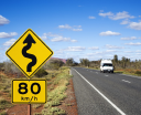 Royalty Free Photo of a Van on a Road in Rural Australia With Speed Limit and Curve Ahead Road Sign
