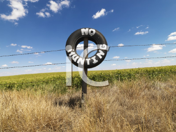 Royalty Free Photo of a Barbed Wire Fence With a Tire Reading No Hunting in Front of a Agricultural Field