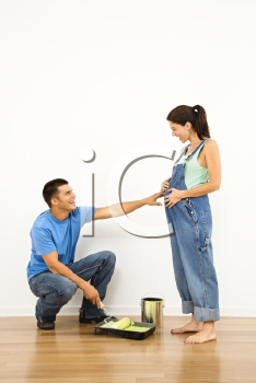 Royalty Free Photo of a Pregnant Woman and Husband Preparing to Paint a Wall