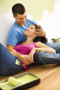 Royalty Free Photo of a Couple Sitting on the Floor Embracing Taking a Break From Interior Painting
