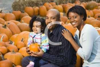 Royalty Free Photo of Parents and Their Daughter Picking Out a Pumpkin and Smiling at an Outdoor Market