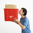 Royalty Free Photo of a Man Standing Kissing a Recycling Bin