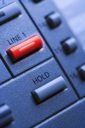 Close up of a multi-line office telephone with lit line one button. Vertical shot.