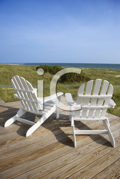 Two Adirondack style chairs sitting on a wooden deck, facing the shore. The grassy beach is in view beyond the deck. Vertical shot.