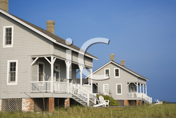 Cropped, low angle view of two identical looking beachfront homes against a backdrop of a clear, blue sky. Horizontal shot.