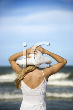 Young woman holds her hat down as she looks out at the ocean from the beach. Vertical shot.