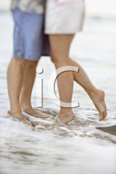 Waist down image of affectionate couple standing in the water at the beach. Vertical shot.
