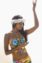 Attractive young Hawaiian woman in tropical flower print summer attire and a lei on her head dancing with hands in hula position.