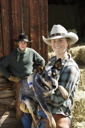 Attractive young woman wearing a cowboy hat and holding an Australian Shepherd. A young man is standing in the background. Vertical shot.