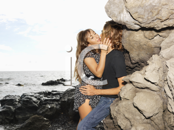Attractive young couple leaning against rocks in a passionate embrace at the coast. Horizontal shot.