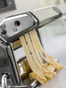 Royalty Free Photo of Fresh Egg Tagliatelle Being Rolled in a Pasta Machine