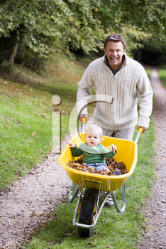 Royalty Free Photo of a Father Pushing a Baby in a Wheelbarrow