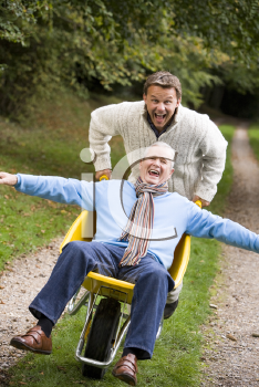 Royalty Free Photo of a Man Pushing Another Man in a Wheelchair