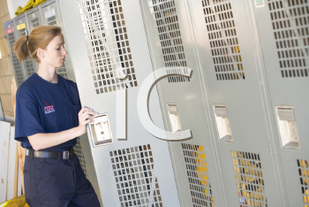 Royalty Free Photo of a Female Firefighter at Her Locker