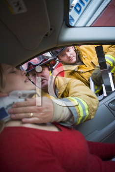 Royalty Free Photo of Firefighters Helping a Car Crash Victim