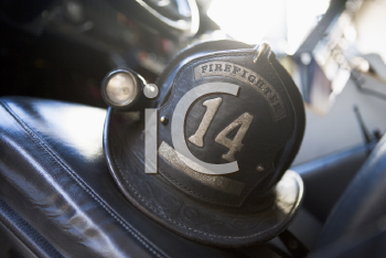 Royalty Free Photo of a Firefighter's Helmet on the Seat of the Firetruck